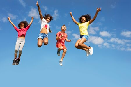 Group of happy kids jump very high over clear sky