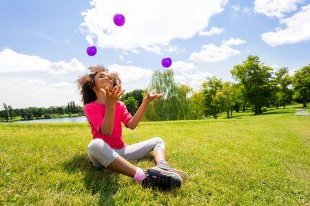 Klein schattig krullend zwart mooi meisje jongleert Stockfoto