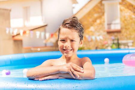 Happy boy smiling portrait on the pool border