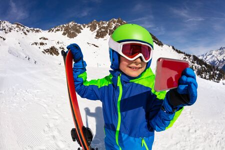 Little boy with ski video call holding smartphone