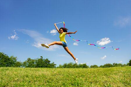 Cute girl long jump waving colorful ribbon