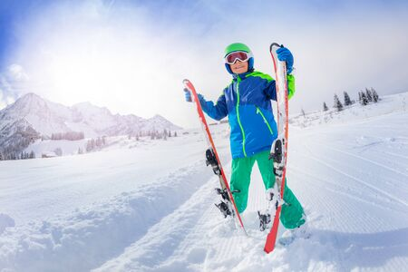 Boy smile, stand on fresh new snow slope with ski