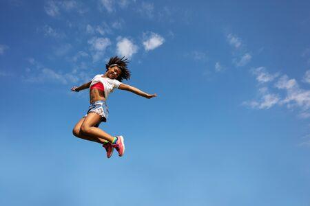 Happy young school age girl jump high over sky Stok Fotoğraf