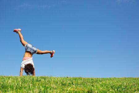 Junge schwarze Mädchen stehen auf den Händen über den Himmel von hinten