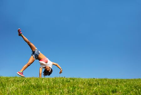 Happy girl walk on hands over blue sky and grass