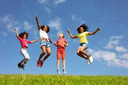 Group of kids jump high over blue sky and clouds