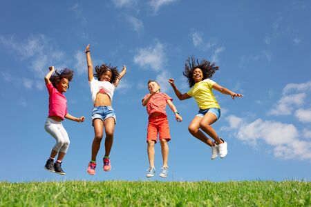 Group of children jump over blue sky and clouds