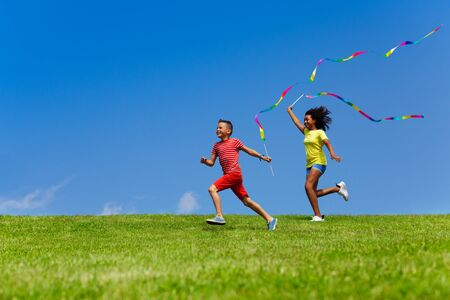 Boy and girl run with long color ribbons over sky