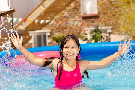 Cute girl splash water in small swimming pool