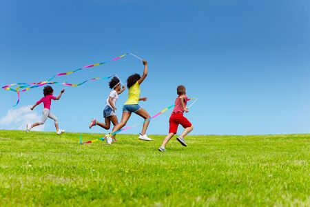 Group of kids run very fast with color ribbons