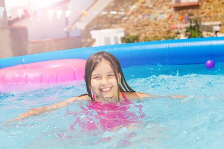 Smiling cute little girl in small swimming pool