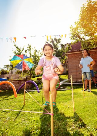 Happy children jumps over strings on playground
