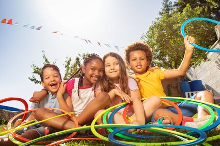 Happy laughing kids sit with hula rings in garden