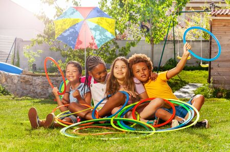Four kids in a group sit with hoops on lawn