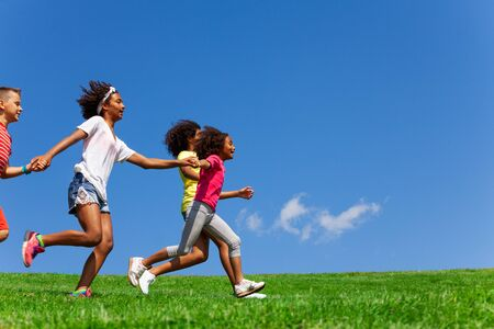 Side portrait of group with fast running kids Stock Photo