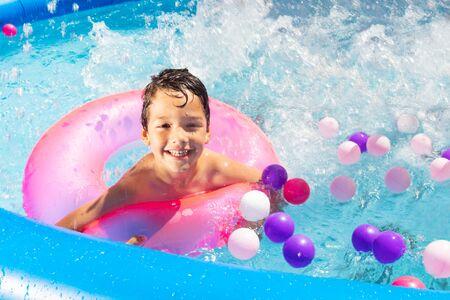 Boy swim splash with buoy ring in swimming pool