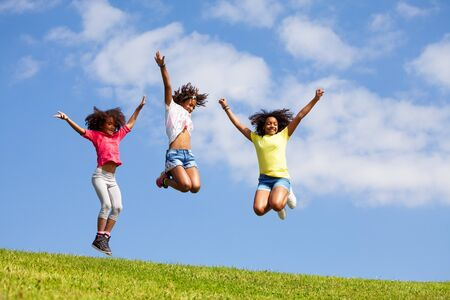 Group three jumping girls over clean blue sky