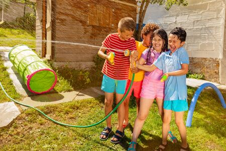 Group of children fight with water gun and spray Banco de Imagens