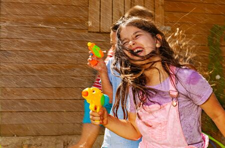 Girl with hair on face play water gun fight game Stock Photo