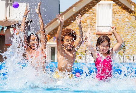 Portrait of three kids splash water in garden pool