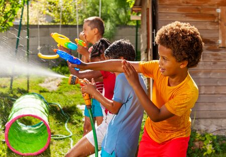 Water gun fight game with many kids in action Stockfoto