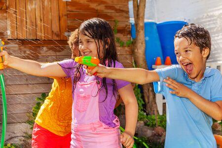 Kids have fun shooting water gun in group game