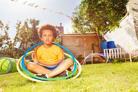 Happy black boy sit with hoop rings on grass