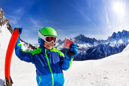 Smiling boy hold ski and take image with his phone