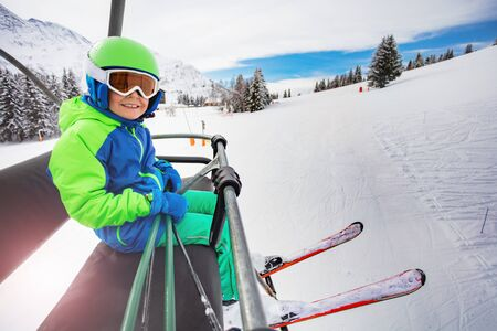 Happy boy on the ski lift with mountain background