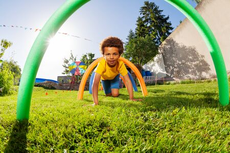 Boy crawl under barriers in a competitive game Imagens