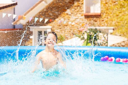 Boy makes big splashes in inflatable swimming pool