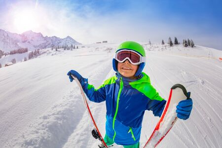 Happy boy on skiing slope hold ski look up smiling