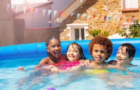 Four happy boys, girls hug sit smile in swim pool