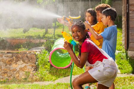 Girl and friends in water gun fight wet fun game