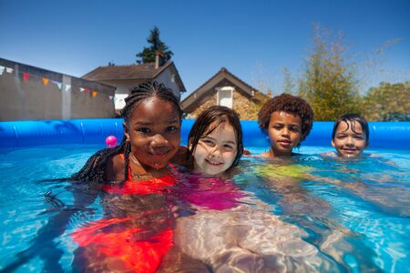 Group small kids friends in swimming pool together