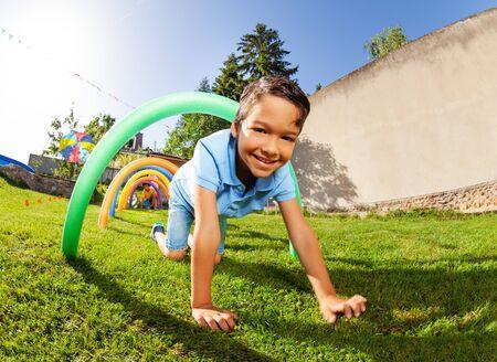 Happy boy portrait pass under course of barriers