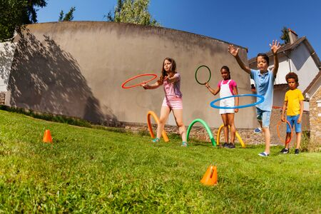 Kids throw ring hoops to target, competitive game Imagens