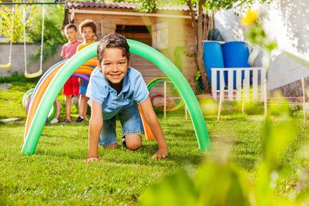 Netter gutaussehender Junge im blauen T-Shirt in einer Gruppe von Kinderfreunden passieren den Spielplatztunnel auf seinen Vieren