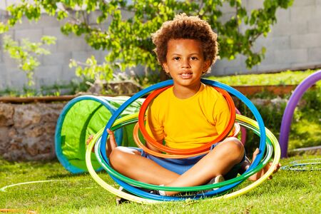 Cute curly boy portrait with color hula hoop rings