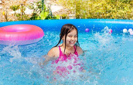 Happy little girl splash water in swimming pool