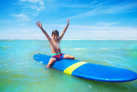 Little boy sit on surfboard with lifted hands up