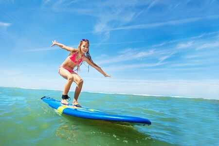 Happy beautiful girl learn to surf on surfboard