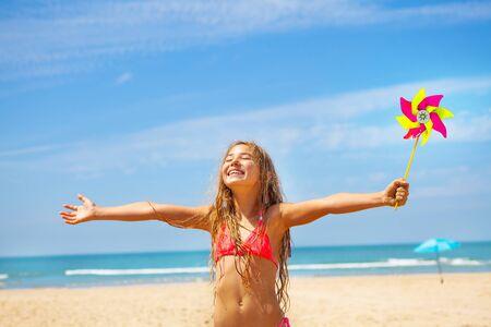 Girl with pinwheel on the beach happy and smiling 版權商用圖片