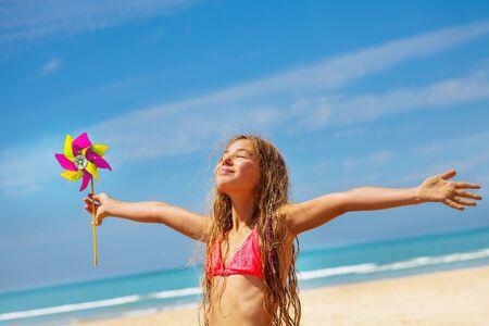 Girl with pinwheel on the beach happy and relaxed