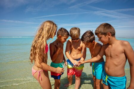 Group of kids circle to check out found seashells Stock fotó