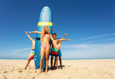 Girl with friends stand by surfboard on the beach 스톡 콘텐츠