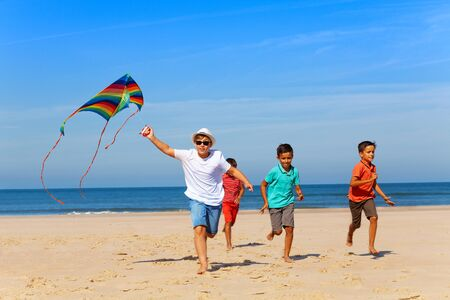 Group of children run on the beach with color kite