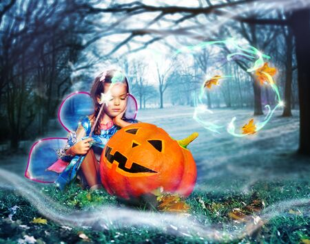 Girl in fee costume cast spells over big pumpkin