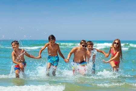 Many kids hold hands and run in the ocean water Stock Photo