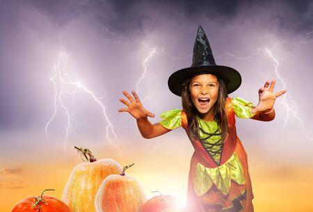 Mädchen beängstigend im Halloween-Kostümstand in der Nähe von Kürbis